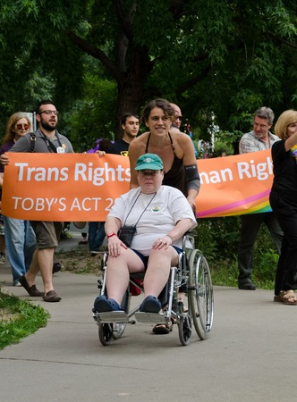 marchers: Wheelchair enabled participant in pride parade Toronto wearing green baseball cap assisted by a woman dressed in a black halter dress passing ahead of marchers walking down a garden path holding banners Editorial