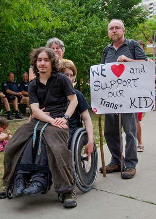transgender: toronto pride parade transgender kid sitting with wheelchair enabled sibling surrounded by supportive parents holding a banner