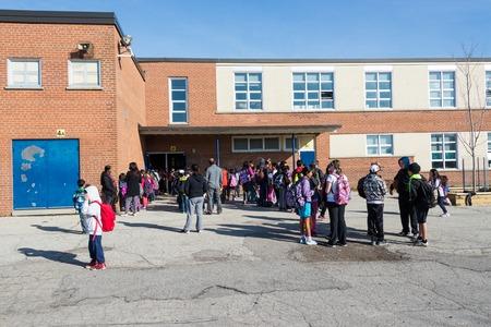 escuela edificio: Escena cotidiana fuera de una escuela media pública: Los padres y los estudiantes esperando en la cola para entrar en la construcción en el primer día de clases algunos estudiantes se amontonan a hablar con sus viejos amigos que otros están haciendo nuevos amigos.