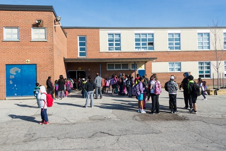 Everyday scene outside a public middle school: Parents and students waiting in line to enter building on first day of school some students crowd together talking to their old friends others are making new friends. Editoriali