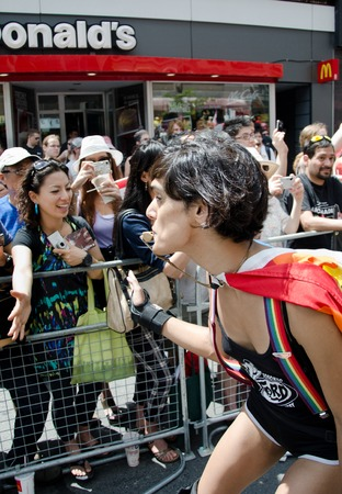 bisexual women: Woman blowing whistle at pride parade Toronto wearing a cape and performing while passing in front of a crowd cheering from the sidelines Editorial
