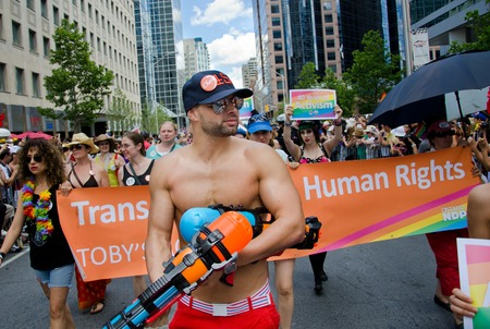 marchers: Shirtless man at pride parade Toronto holding water gun and wearing a black baseball cap and sunglasses walking ahead of marchers walking down the street holding banners with buildings visible on the sides