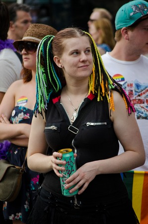 medium shot: Woman at pride parade Toronto wearing multicolored hair wrap strings with people in the background medium shot Editorial