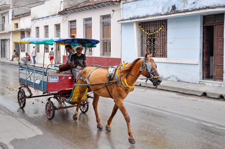 incidental people: A horse drawn 4wheeled passenger carriage moving on a street in Cuba. Horse drawn carriages are used as common means of transport in Cuba. Editorial