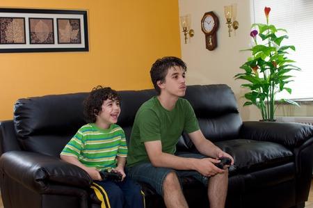 jugando videojuegos: Peque�o hermano y hermano mayor que juega feliz videojuegos juntos en el sof� casa. Por el aspecto de su enorme sonrisa, parece que el ni�o adorable est� ganando! Foto de archivo