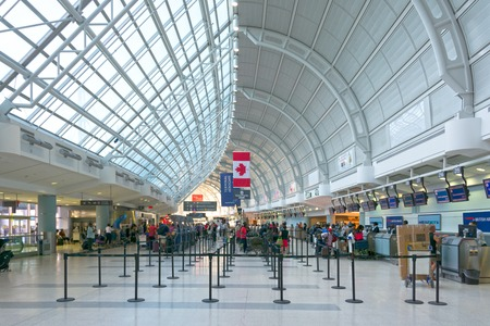 ticketing: Inside view of the huge metal framed Lester B. Pearson international airport. People standing in queues with their baggage at the ticketing counters Editorial
