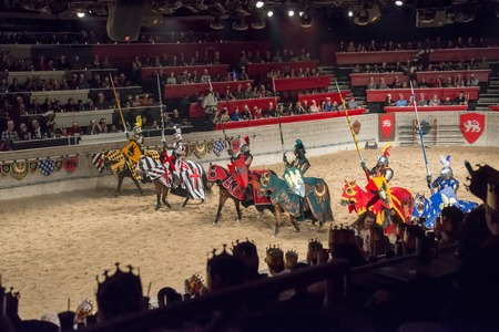 jousting: Medieval Times Restaurant: Six horsemen at a jousting event dressed as medieval knights holding lances lined up in a stadium full of spectators waiting to begin the show