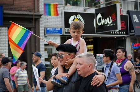 marchers: Couple with a child on shoulder at pride parade in Toronto their closeup waving flag amidst a crowd of marchers in the background Editorial