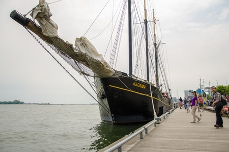 incidental people: Tall sail ship or tourist cruise moored in the city harborfront.