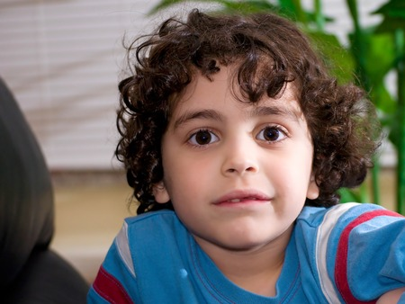 fair skin: Adorable little boy with big brown eyes and curly dark hair and light fair skin smiles for the camera Stock Photo
