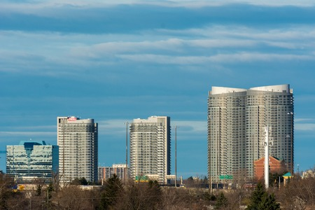highrises: Gorgeous view of modern city highrise condo buildings against a backdrop of a bright blue sky with some beautiful white clouds. Editorial
