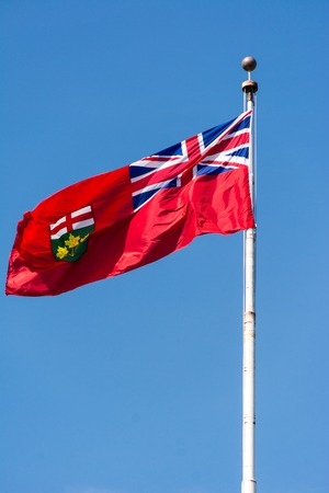 canada aboriginal: Flag of Ontario waving in the wind on a flag pole during blue skies at an upward angle