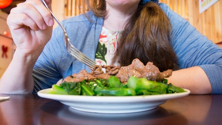 Chinese beef with rapini over green vegetable on white plate reflecting on dark brown wood table in front of woman holding a fork wearing a blue shirt with hair draped over her left shoulder with picture taken from a front angle at a Chinese restaurant. photo
