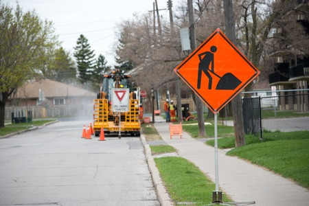 warns: Bright orange traffic sign warns of construction ahead with construction equipment in the background. Stock Photo