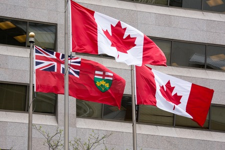 canada flag: The national flag of Canada and Ontario flag waving or flying in the wind. Windows of  modern building on the background.