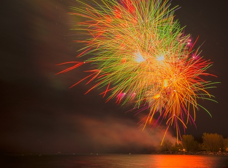 blast off: Colorful fireworks in the dark, night sky reflecting off the water below Stock Photo