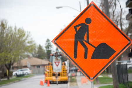 street signs: Bright orange traffic sign warns of construction ahead with construction equipment in the background. Stock Photo