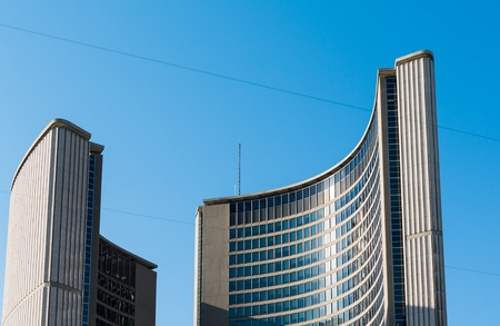 The Modernist architecture of the New City Hall in Nathan Phillips Square in day light afternoon against the backdrop of bright blue sky