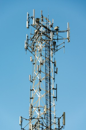 Cell phone communication tower with multiple antennas against a blue sky