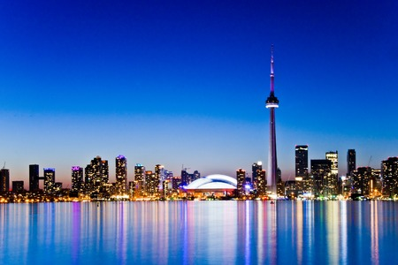 Skyline of Toronto, Canada, featuring the CN tower, at dusk with lights reflecting on the water. Editorial