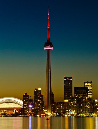 The CN tower above the Toronto skyline at dusk reflected in the water.