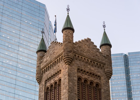 Contrasting Toronto Architecture: Castle shaped vintage building catholic church against the modern glass facade skyscrapers. Imagens - 43187503