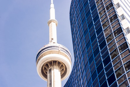 building cn tower: Close-up of CN tower and condo Building against clear blue sky.Tallest and largest residential building or condominium in Canada, CN Tower is the worlds 6th tallest free-standing structure. Editorial