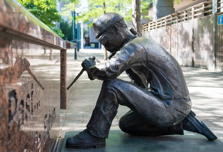anonymity: The Anonymity of prevention bronze statue showing a worker working with a chisel and hammer with safety goggles at WSIB Simcoe Park Workers Monument, Toronto.  This bronze sculpture by artists Derek Lo & Lana Winkler was commissioned by the Workplace Safe Editorial