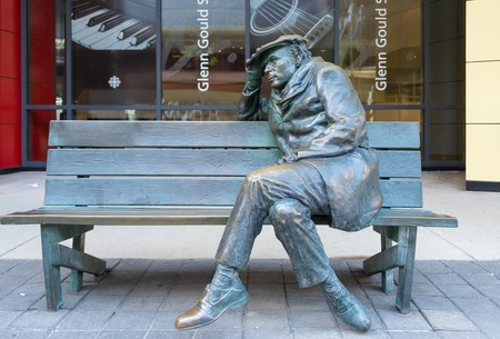 Life-sized bronze statue of Glenn Gould, sitting on a park bench outside the CBC Building in downtown Toronto. Editorial