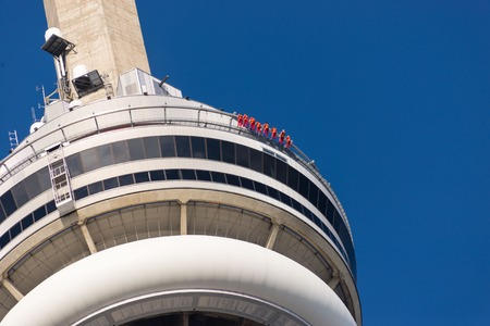 building cn tower: Closeup of the CN tower showing people edge-walking around the edge of the building. Edge Walk is Toronto�s newest and tallest urban adventure and the world�s highest full circle hands-free walk. The CN Tower is a 553.33 meter high concrete communications Editorial
