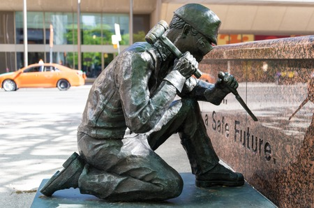 anonymity: WSIB Simcoe Park Workers Monument: The Anonymity of prevention bronze statue showing a worker working with a chisel and hammer with safety goggles. This bronze sculpture by artists Derek Lo & Lana Winkler was commissioned by the Workplace Safety & Insuran Editorial