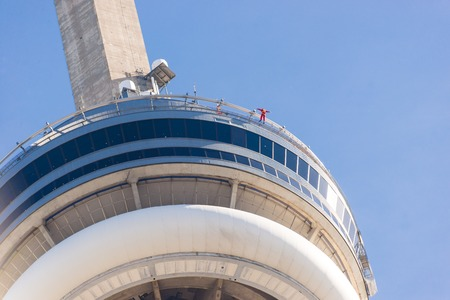 building cn tower: Close-up of CN tower showing person edgewalking around the edge of the building. EdgeWalk is Toronto�s newest and tallest urban adventure and the world�s highest full circle hands-free walk.