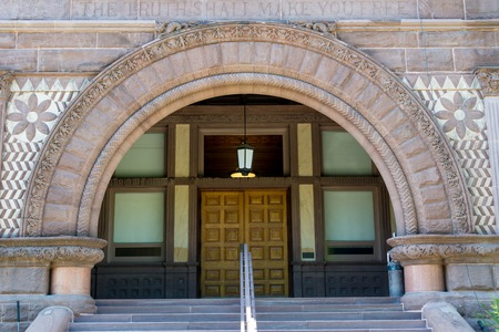 gothic build: Close up of the semi circular stone carved arch with stairs leading to it at the  University of Toronto.