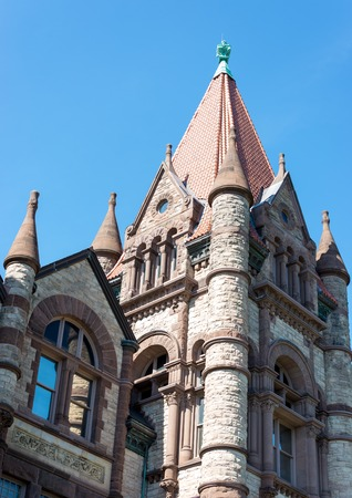 The castle shaped historic building of Victoria College at university of Toronto. The building has cylindrical pillars on corners with cone structure on the top. Imagens - 43260196