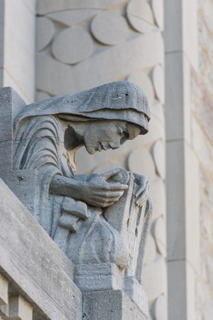 leaning forward: Sculpture of a lady leaning forward on the exterior wall of the University of Toronto building. Stock Photo