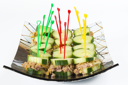 botanas: Healthy snack for diabetics: tuna and cucumber sandwiches or finger foods made of tuna sandwiched  in cucumber slices, arranged in a decorative curved glass plate.