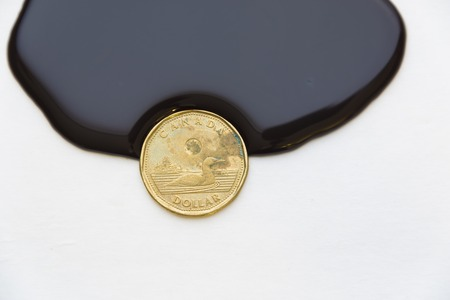 canadian coin: Canadian dollar a petro dollar currency:Thick black liquid about to engulf a coin. A one dollar Canadian coin is in way of a dense black flowing liquid.