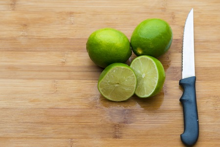 two and a half: Lime placed on a wooden chopping board with a knife. There are two whole lime and two half cut pieces.