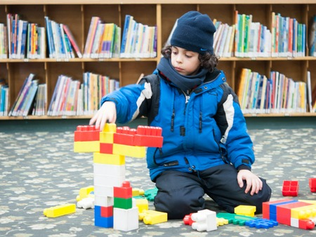 he is public: Boy playing with Legos in Toronto Public Library.  He is wearing a blue jacket and black hat, while stacking multicolored blocks on top of each other.  He is sitting on the floor of a library, with several bookshelves in the background.