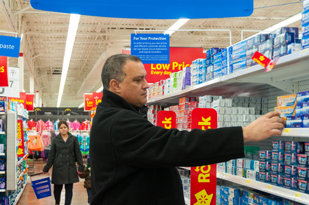walmart: Man shopping  at Wal-Mart. He is wearing a black shirt and examining toothpastes.  Red and blue signs surround him and the woman who stands behind him.