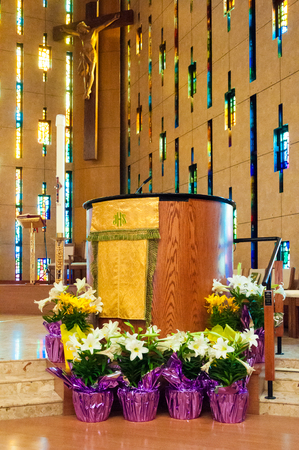 Inside details of Annunciation Catholic Church. Mass podium and Christ cruxified image in background. Sunlight filters through stained glass windows over a wooden altar decorated with white flowers.