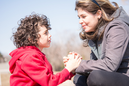Christian faith in action: mother and son outdoors devotional. Godly relationship in a small Hispanic family.Woman and child kneel and hold hands.  The woman has shoulder-length brown hair, sunglasses on her head, and a gray jacket.  Her son has curly dar photo