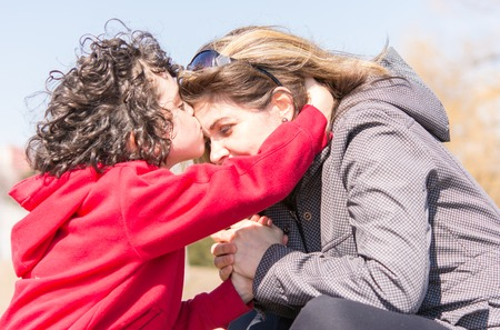 Christian faith in action: mother and son outdoors devotional. Godly relationship in a small Hispanic family.Boy embracing and kissing mothers forehead.  He has dark curly hair and wears a sweatshirt as he embraces his mother, a woman with shoulder-lengt Stock Photo