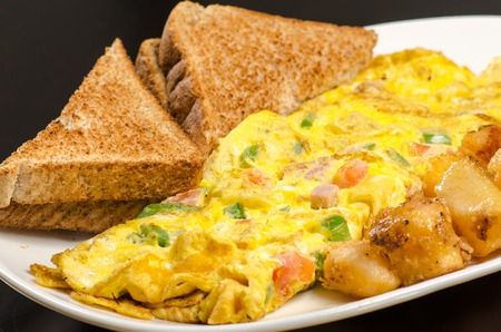 either: Omelet with a side of breakfast potatoes and toast.  A whte plate is laden with a ham, chive, and tomato omelet.  Golden brown toast and a serving of potatoes sit on either side of the omelet.
