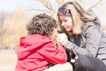 Christian faith in action: mother and son outdoors devotional. Godly relationship in a small Hispanic family.The woman has shoulder-length brown hair, sunglasses on her head, and a gray jacket.  Her son has curly dark hair and a red sweatshirt.
