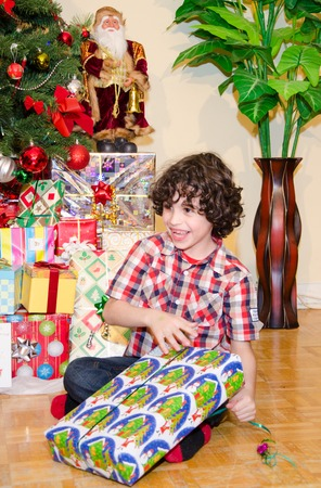 unwrapping: Real life Christmas scenes: Boy opening Christmas presents.  A boy with curly dark hair and a checkered shirt tears through white wrapping paper decorated with green houses, santas, and snowmen.  Christmas decorations, including a tree and a statue of San Stock Photo