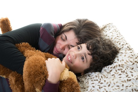 Little boy lying on the bed holding his mother tightly with one hand and a soft toy with the other hand, against white background. The boys seems little frightened while his mother is sleeping with eyes closed. photo