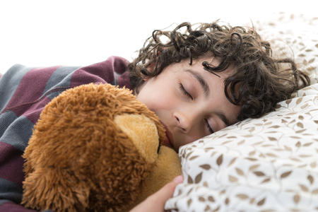 Boy sleeping on bed holding a soft toy by his side, against white background. The photo represents innocence of children.