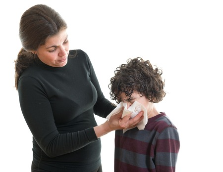 Mother cleaning nose of her child using a white handkerchief, against white background. The woman is dressed in complete black. photo