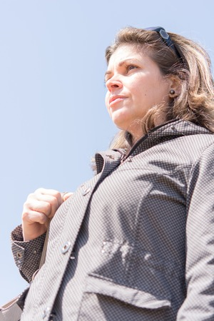 Woman looking into the distance.  She is standing above the photographer, and looking into a blue sky.  She has shoulder-length brown hair, and wears a gray jacket and sunglasses on top of her head. photo